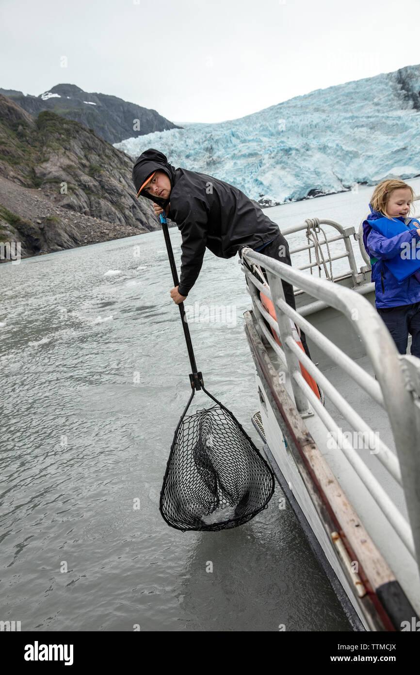 USA, Alaska, Seward, playing with chucks of glacial ice from Holgate Glacier seen while exploring Resurrection Bay Stock Photo