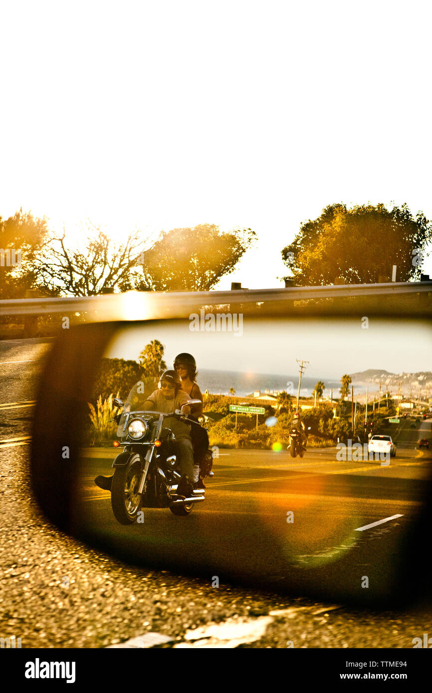 USA, California, Malibu, a couple on a motorcycle cruises along the Pacific Coast Highway at the end of the day - Stock Image