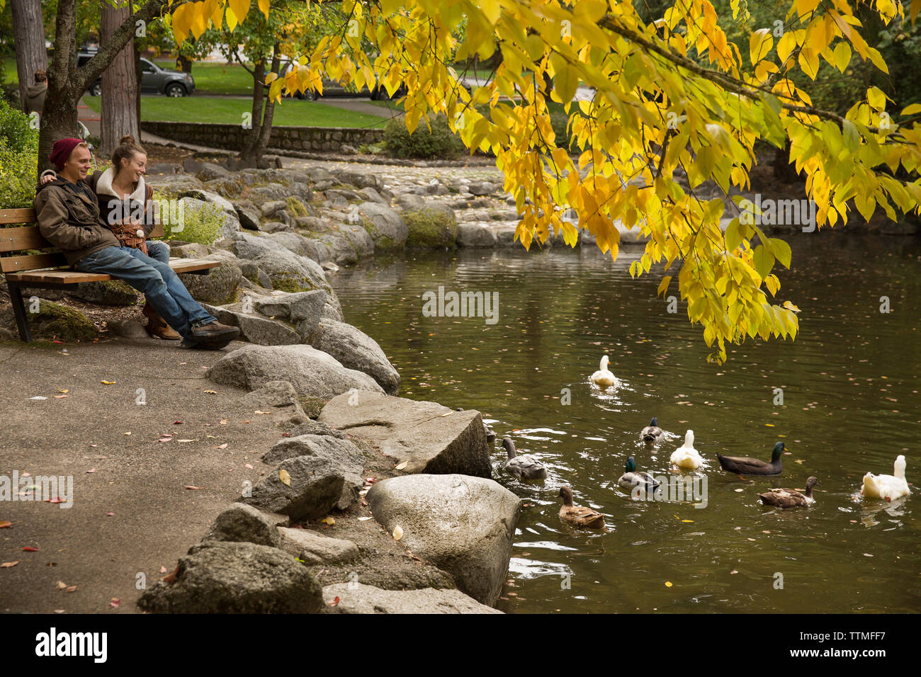 USA, Oregon, Ashland, a couple sit and watch the ducks swim in the Lithia River in Lithia Park - Stock Image