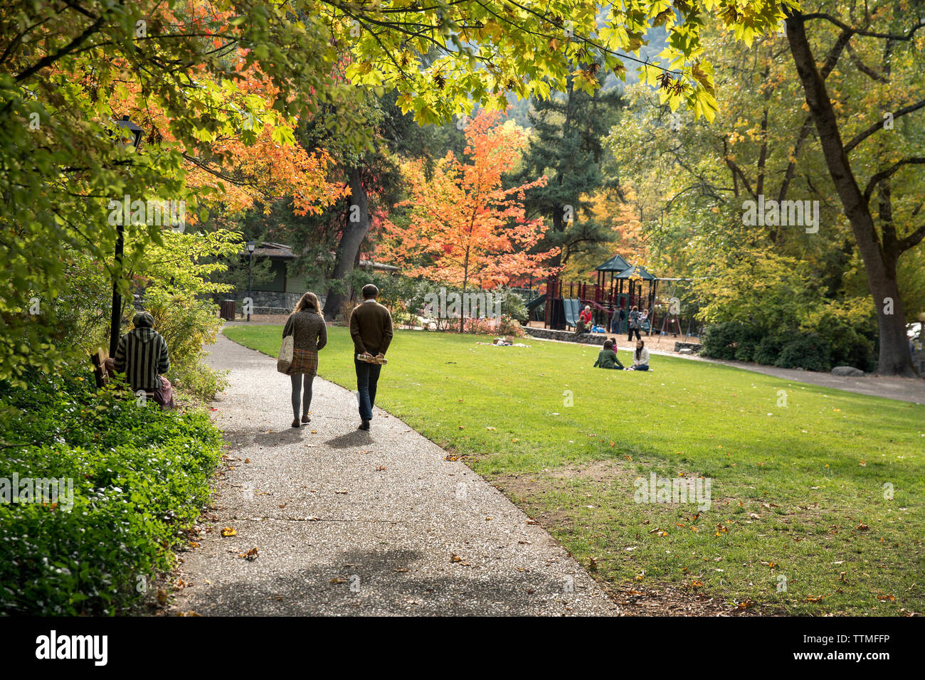 USA, Oregon, Ashland, a young man and woman walk through Lithia Park in the Fall - Stock Image