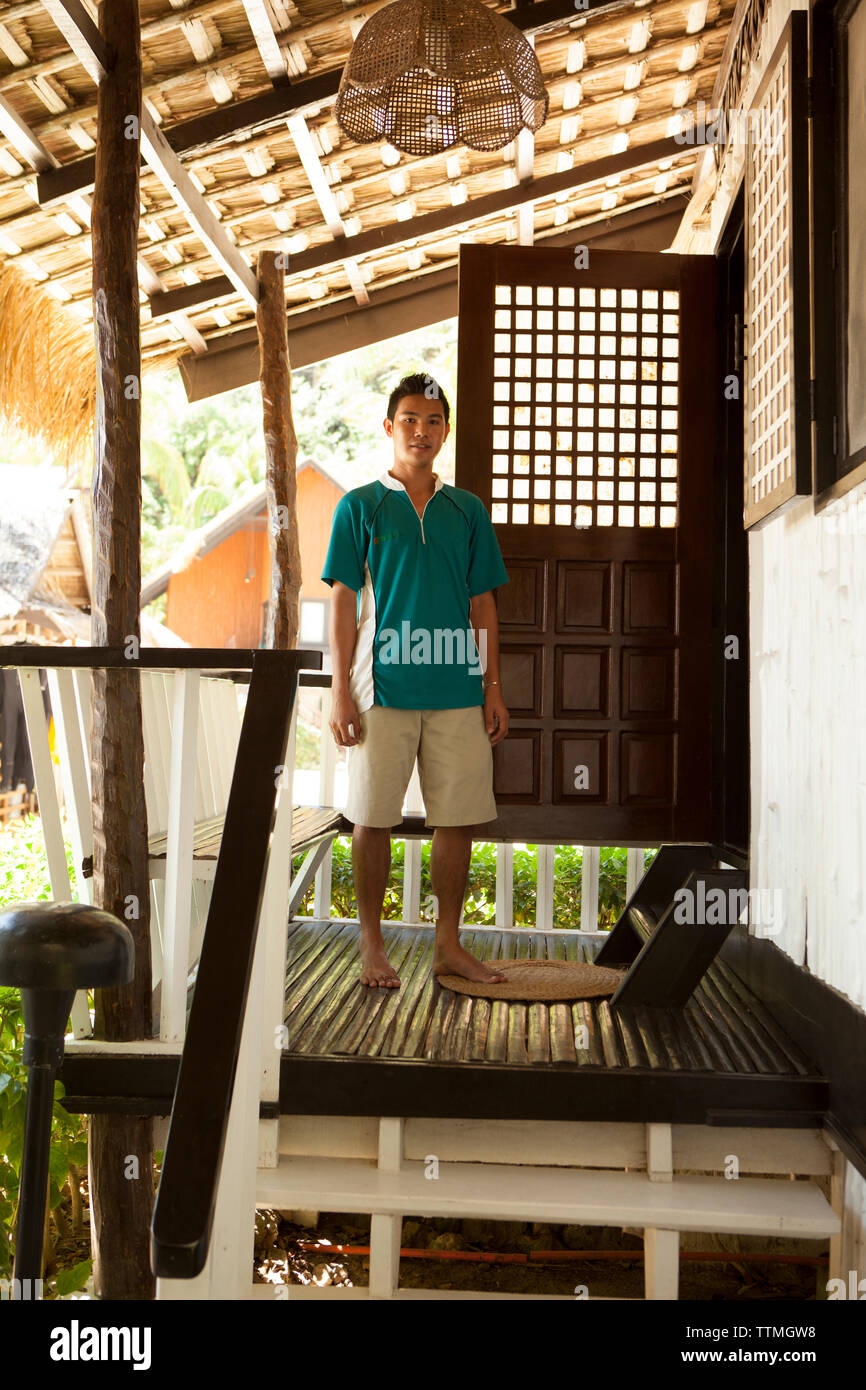 PHILIPPINES, Palawan, El Nido, a young man stands in front of one of the cottages at Miniloc Island Resort, Bacuit Bay in the South China Sea - Stock Image