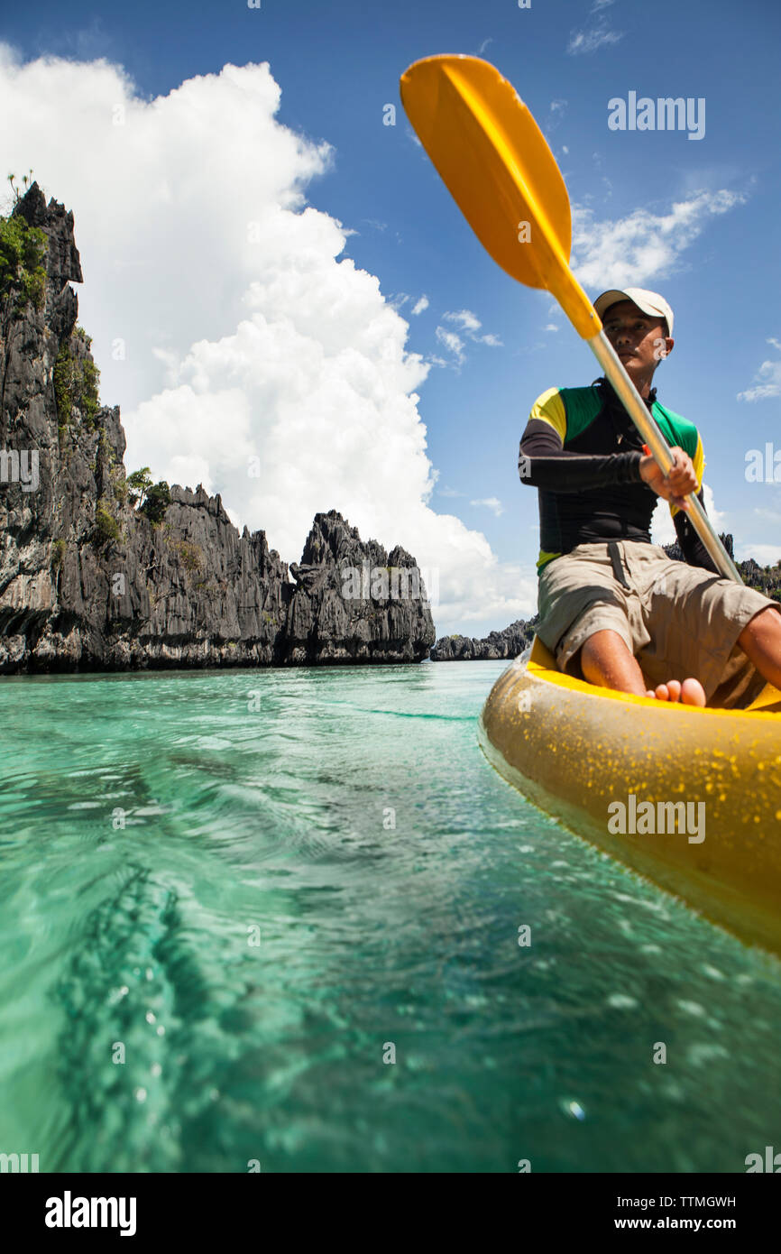 PHILIPPINES, Palawan, El Nido, Miniloc Island, a local from El Nido kayaks through the crystal clear waters of Small Lagoon on Miniloc Island located - Stock Image