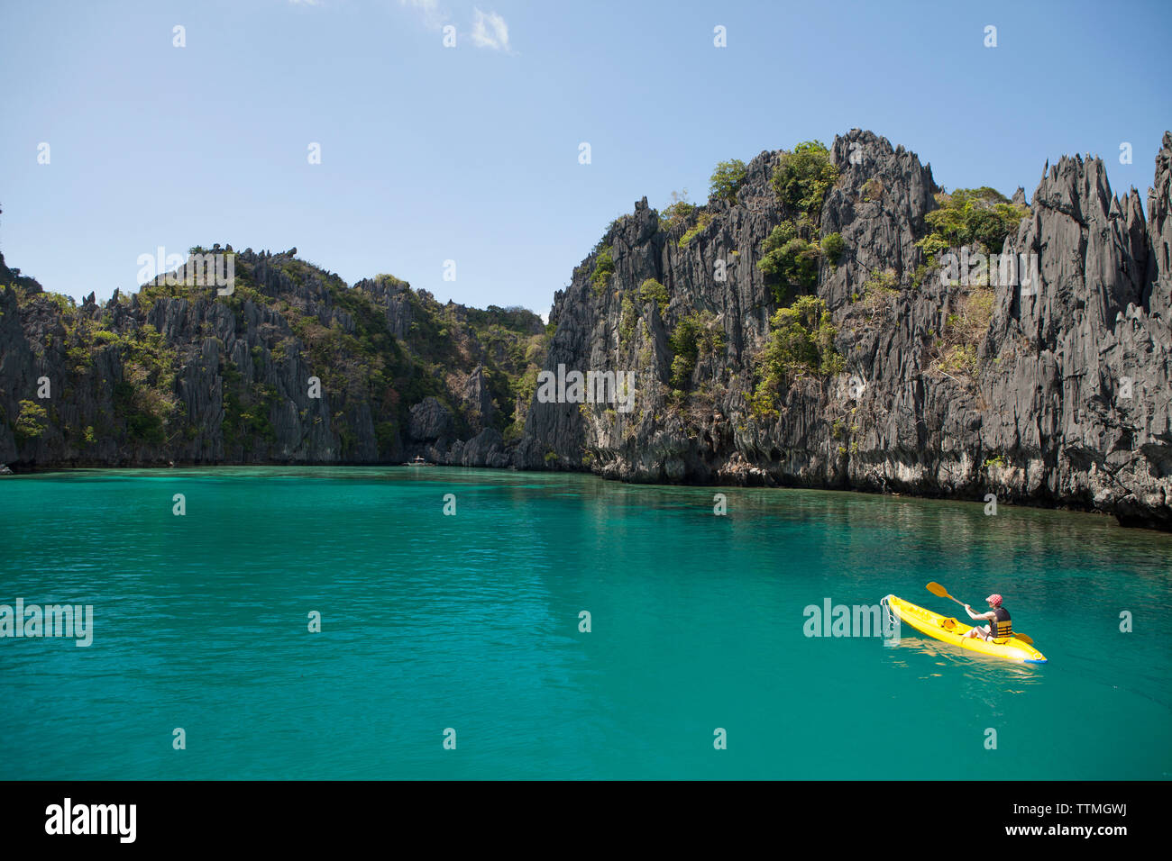 PHILIPPINES, Palawan, El Nido, Miniloc Island, a woman kayaks through the crystal clear waters of Small Lagoon on Miniloc Island located in Bacuit Bay - Stock Image