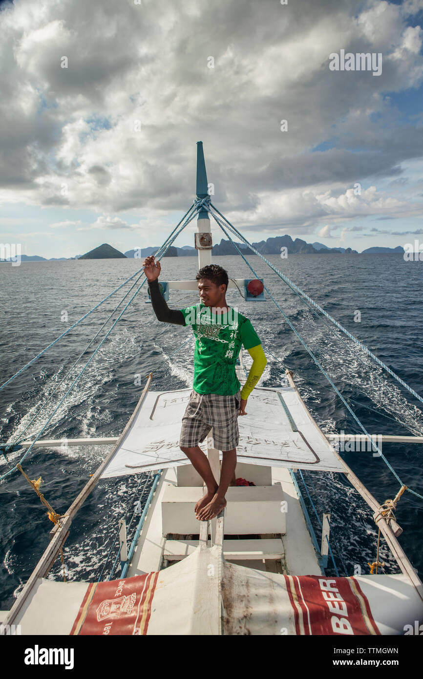 PHILIPPINES, Palawan, El Nido, Lagen Island, deck hand Eric keeps watch on a trip from Lagen Island to Miniloc in Bacuit Bay in the South China Sea - Stock Image