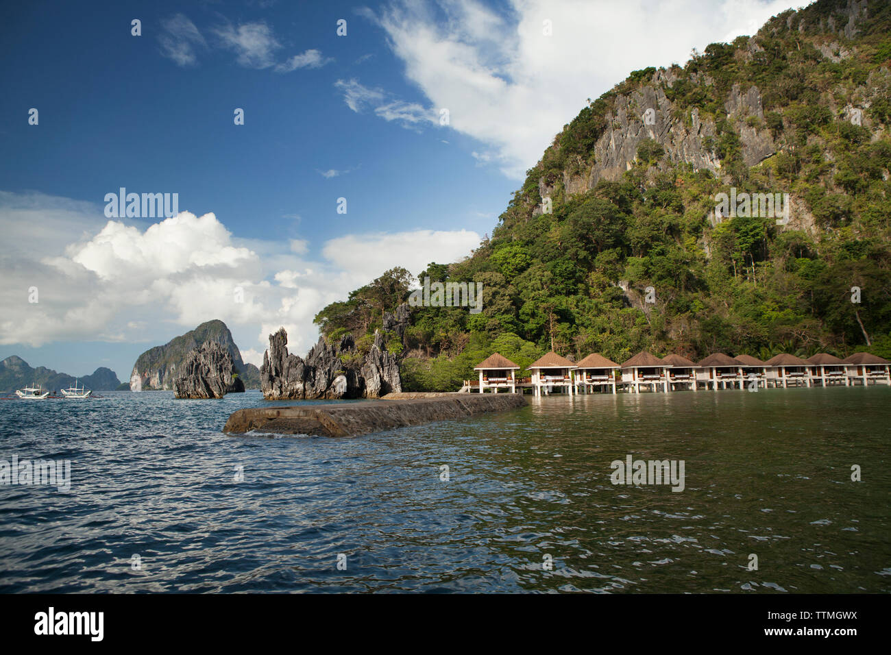 PHILIPPINES, Palawan, El Nido, Lagen Island, view of surrounding rock formations, a fishing boat and Lagen Island Resort cottages in Bacuit Bay in the - Stock Image