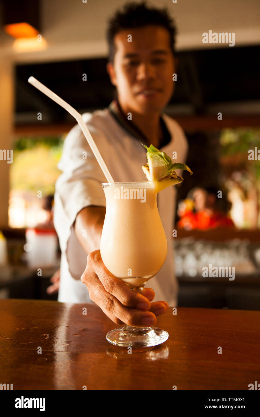 PHILIPPINES, Palawan, El Nido, Lagen Island, bartender serves a pina colada at Lagen Island Resort in Bacuit Bay in the South China Sea - Stock Image