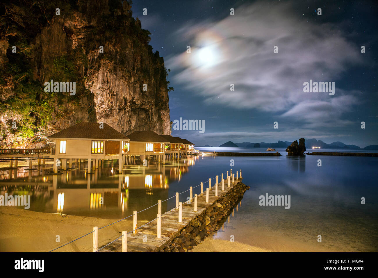 PHILIPPINES, Palawan, El Nido, night view of the Lagen Island Resort cottages which sit over the water and below the rocky cliffs, Bacuit Bay in the S - Stock Image