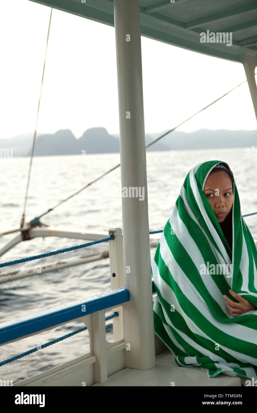 PHILIPPINES, Palawan, El Nido, Lagen Island, an employee and resident of El Nido takes the boat from Lagen Island Resort to El Nido, Bacuit Bay, the S - Stock Image