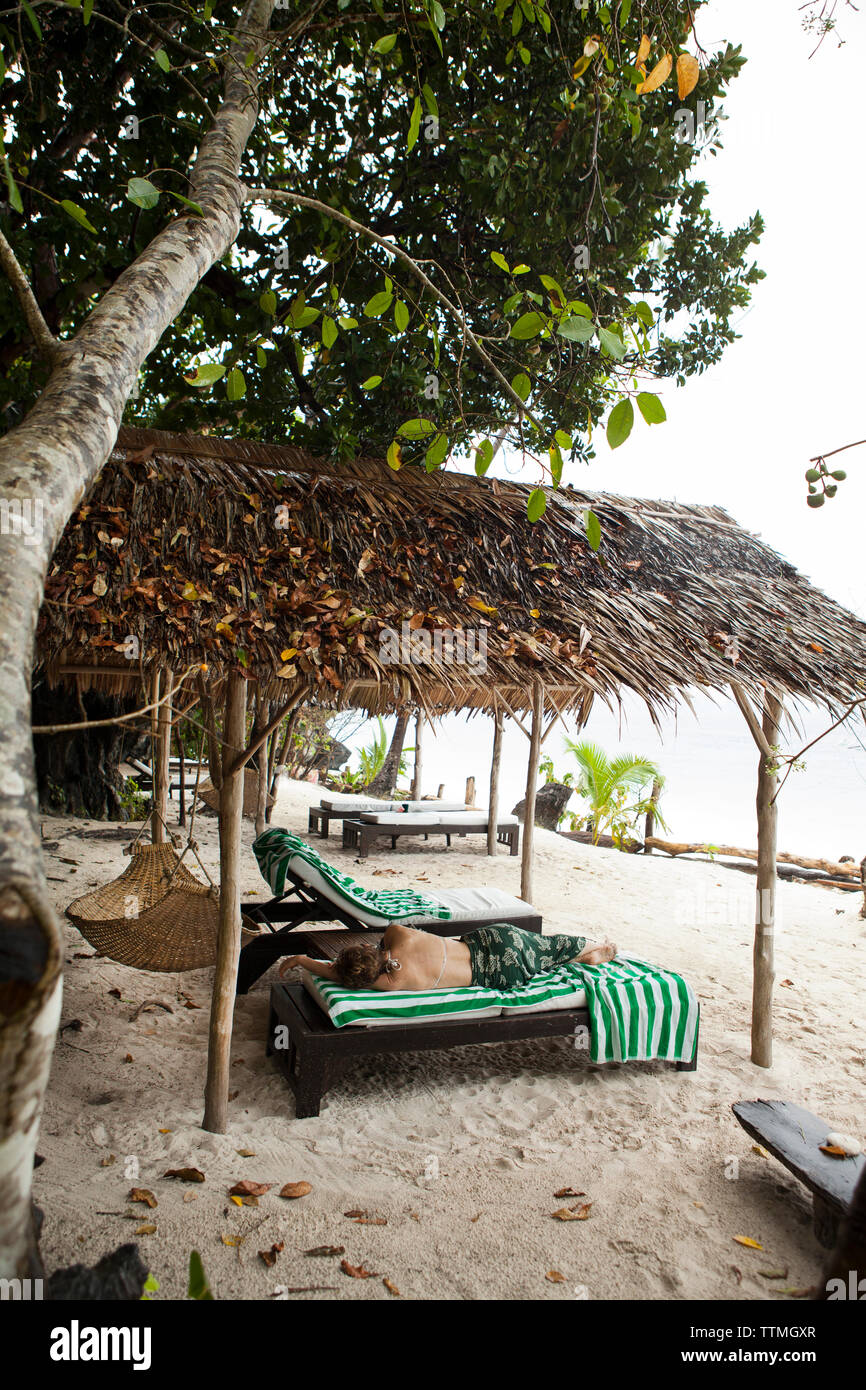 PHILIPPINES, Palawan, El Nido, Entalula Island, a woman takes a rest on Entalula Island located in Bacuit Bay in the South China Sea - Stock Image