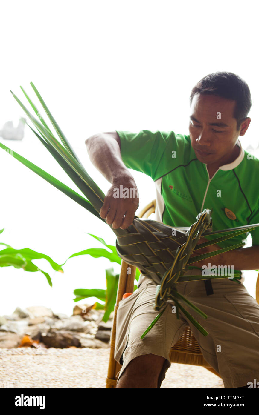 PHILIPPINES, Palawan, El Nido, Lagen Island, a man weaves a hat out of palm leaves at Lagen Island Resort, Bacuit Bay in the South China Sea - Stock Image
