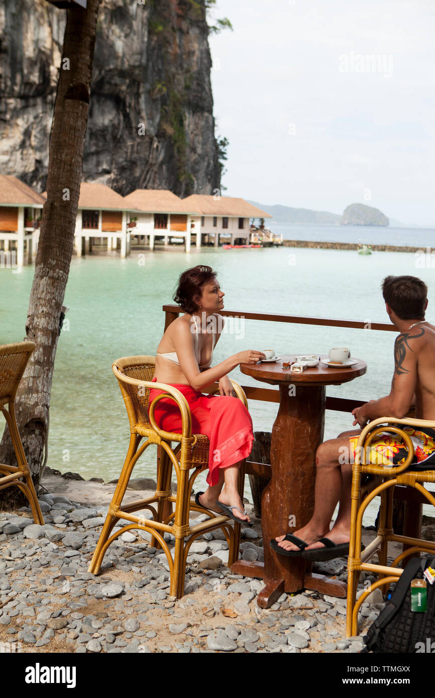 PHILIPPINES, Palawan, El Nido, Lagen Island, a couple has breakfast by the pool at the Lagen Island Resort in Bacuit Bay in the South China Sea - Stock Image