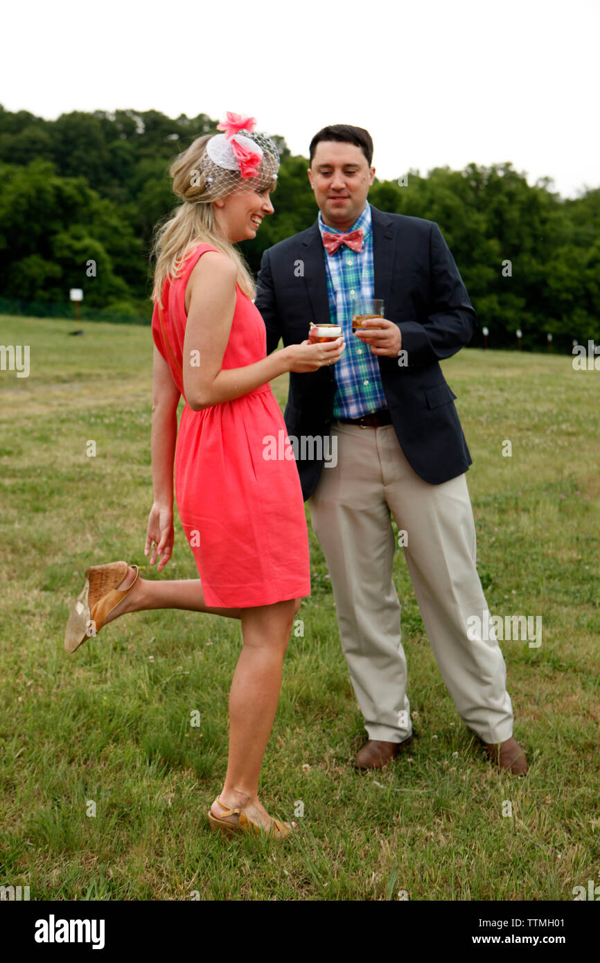 USA, Tennessee, Nashville, Iroquois Steeplechase, a young man and woman drink Moonshine Cherry-Basil Blush and Tennessee Whiskey - Stock Image