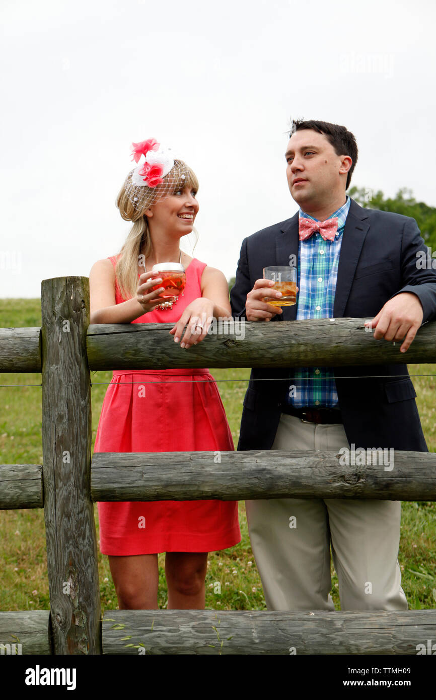 USA, Tennessee, Nashville, Iroquois Steeplechase, a young man and woman by a fence drinking Moonshine Cherry-Basil Blush and Tennessee Whiskey - Stock Image
