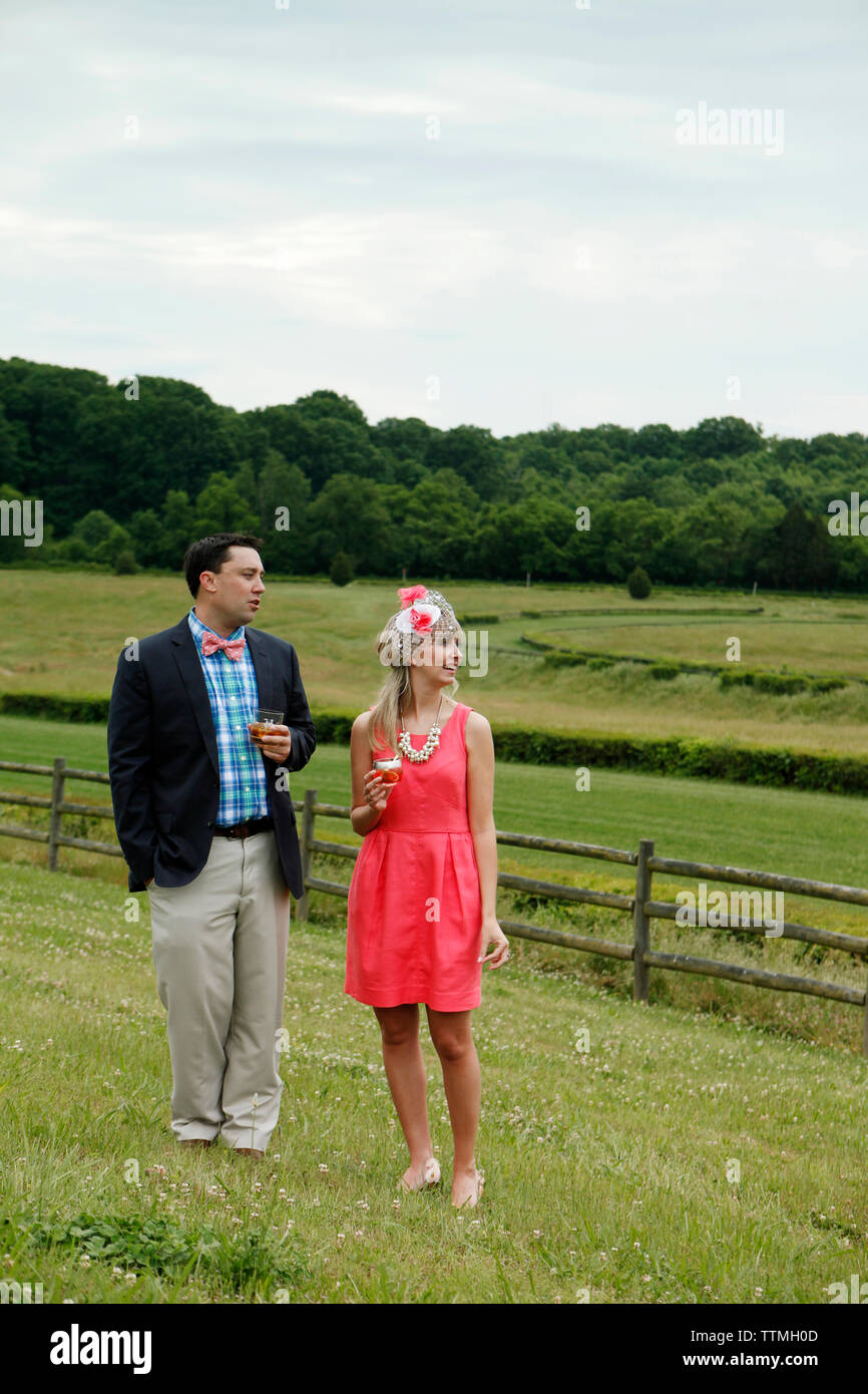 USA, Tennessee, Nashville, Iroquois Steeplechase, a young man and woman stand by the race track drinking Moonshine Cherry-Basil Blush and Tennessee Wh - Stock Image