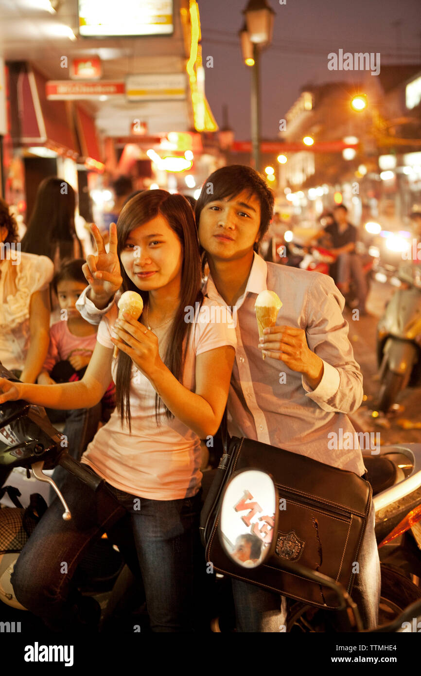 VIETNAM, Hanoi, a sweet young couple sits on their moped eating ice cream on a hot Summer night in downtown Hanoi - Stock Image