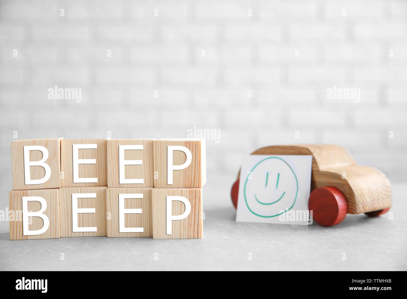 Cubes with words BEEP BEEP and toy car on brick wall background - Stock Image