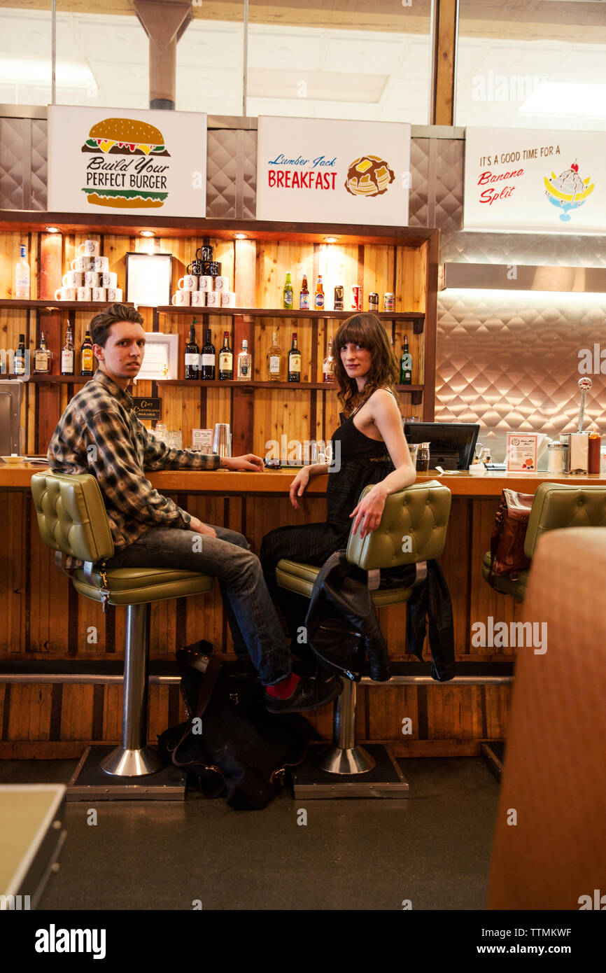 CANADA, Vancouver, British Columbia, A local couple dine at the counter, Save On Meats Restaurant located on West Hastings Street - Stock Image