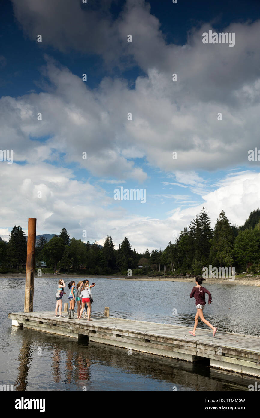 CANADA, Vancouver, British Columbia, young girls gather on the dock at Port Graves, Gambier Island in the Howe Sound - Stock Image