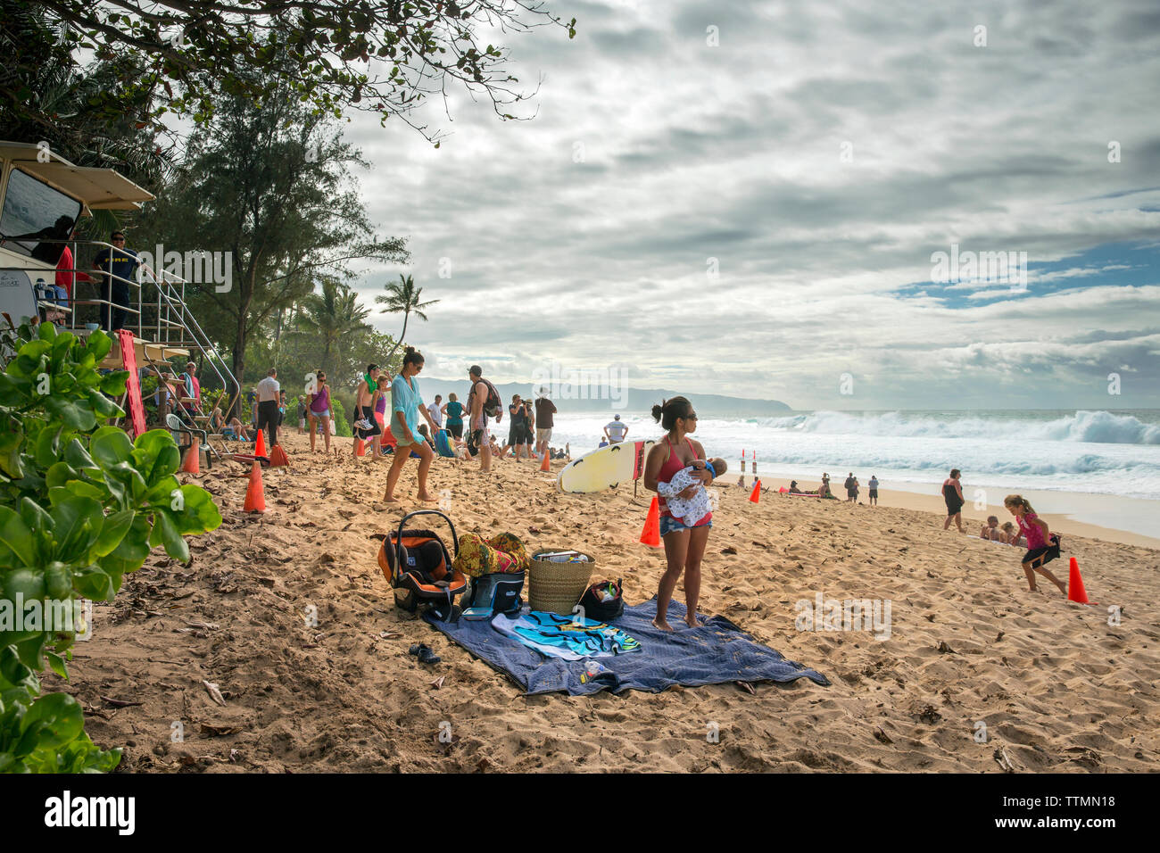USA, HAWAII, Oahu, Northshore, families gather on the beach at Pipeline - Stock Image