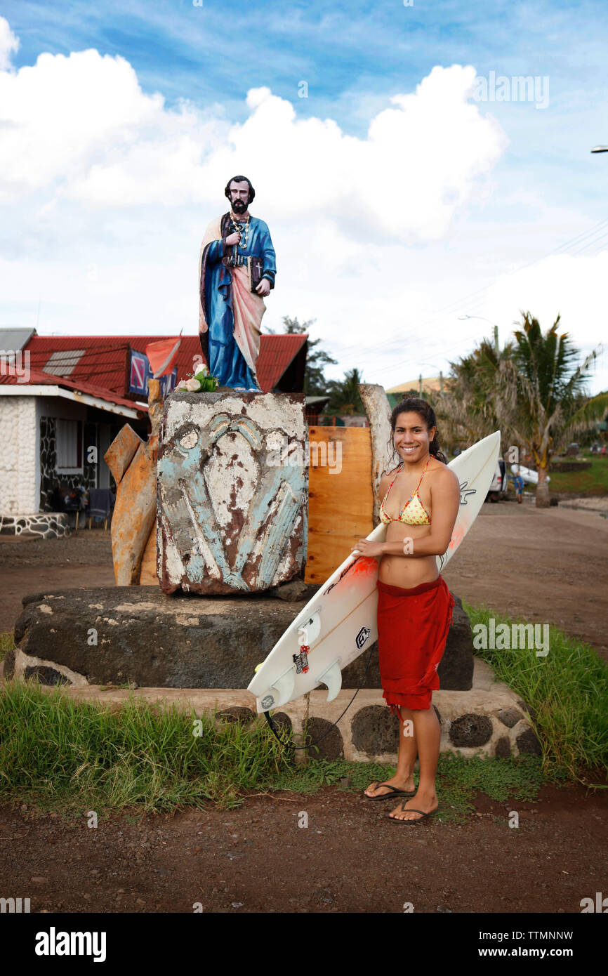 EASTER ISLAND, CHILE, Isla de Pascua, Rapa Nui, a woman stands with her surfboard near a statue in the heart of downtown Hanga Roa - Stock Image