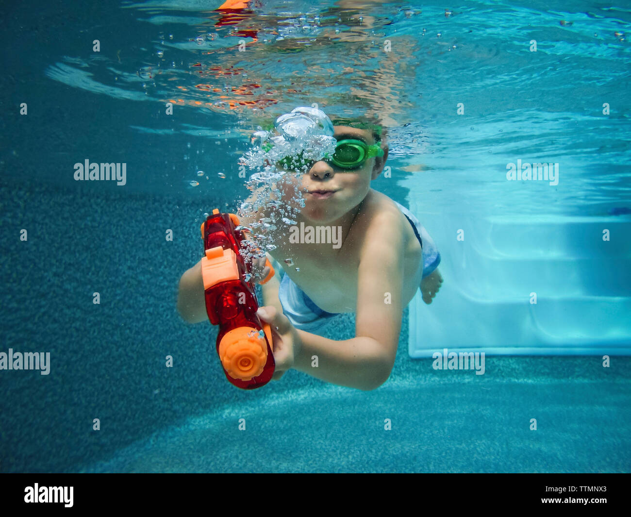 Playful shirtless boy with squirt gun swimming in pool - Stock Image
