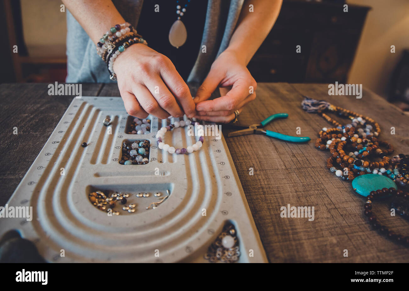 Midsection of woman using beading board while making bracelets while standing by table at home - Stock Image