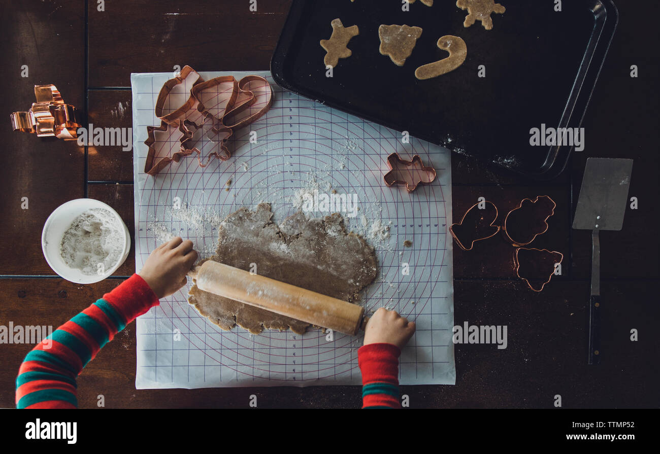 Cropped hands of boy rolling cookie dough on table during Christmas at home - Stock Image