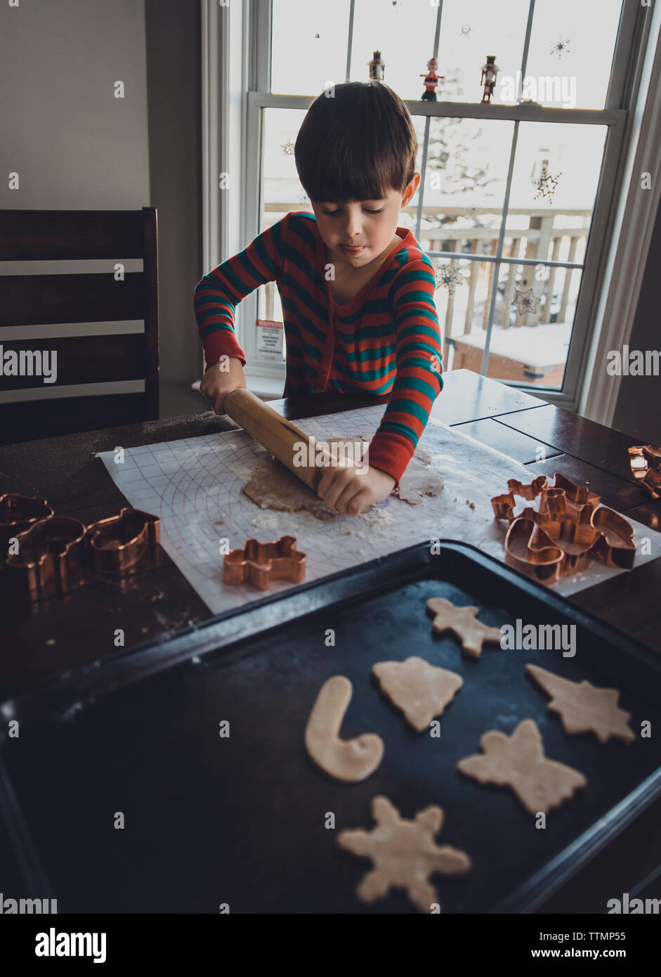 Boy rolling cookie dough on table during Christmas at home - Stock Image
