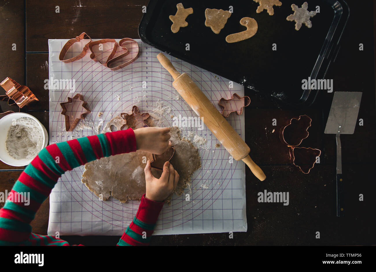 Cropped hands of boy using pastry cutter while making cookies on table during Christmas at home - Stock Image