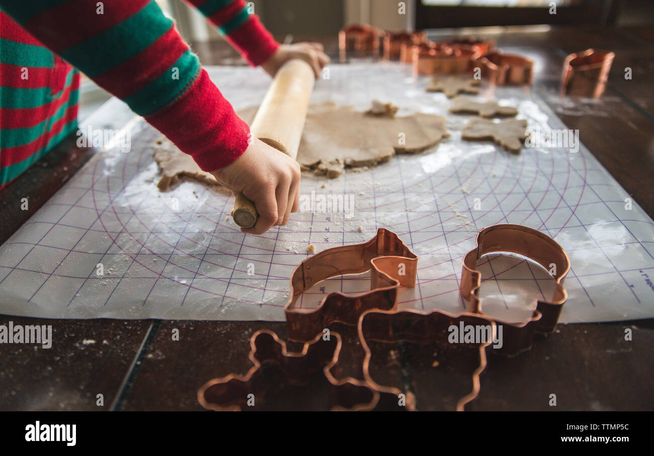 Close-up of boy rolling cookie dough on table during Christmas at home - Stock Image