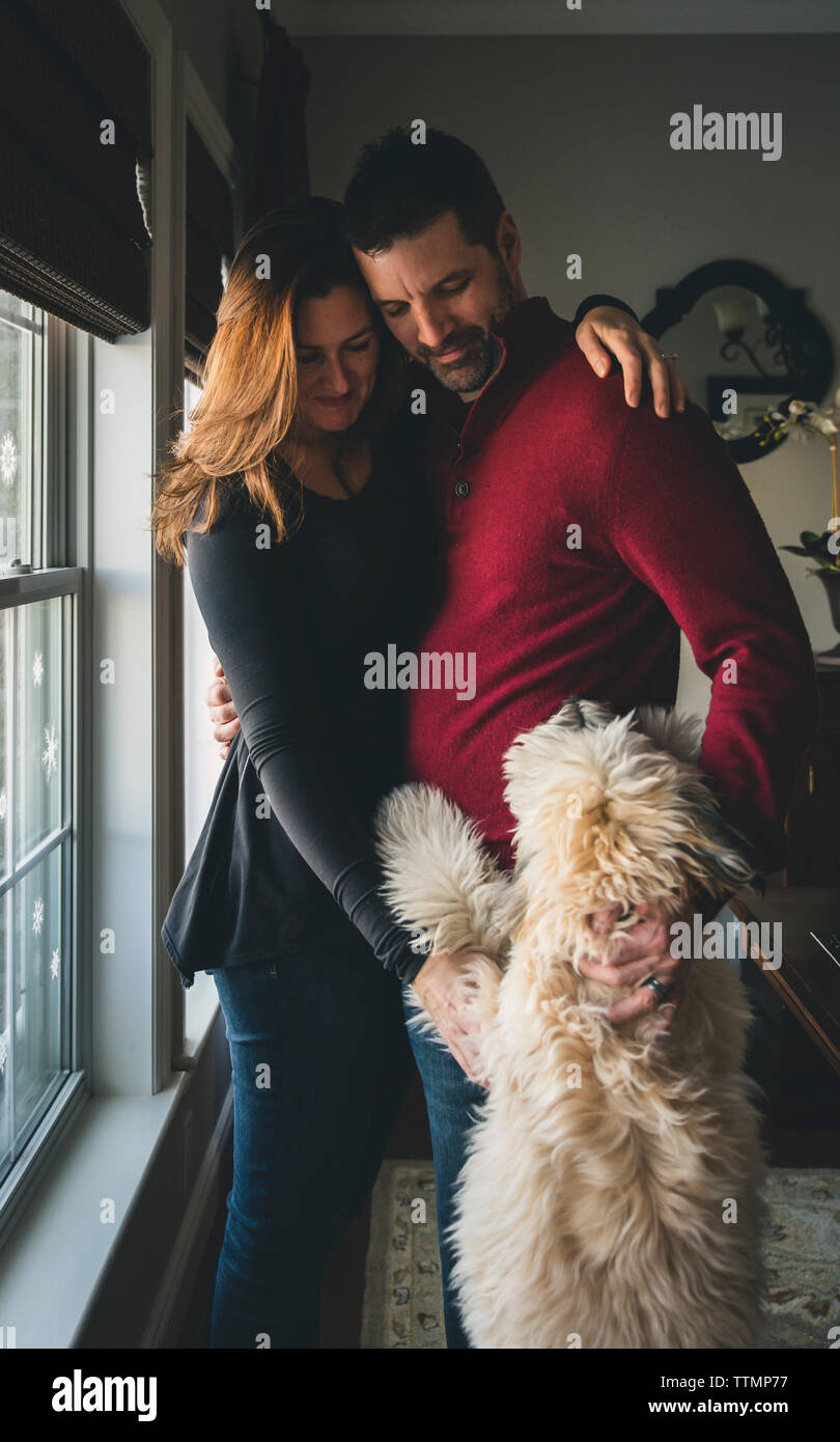 Couple with dog standing by window at home - Stock Image