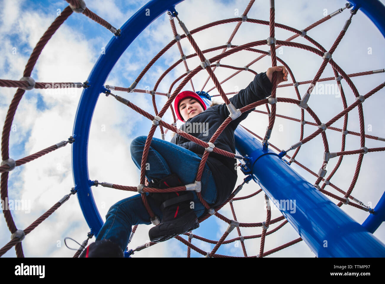 Low angle portrait of boy climbing merry-go-round against cloudy sky - Stock Image