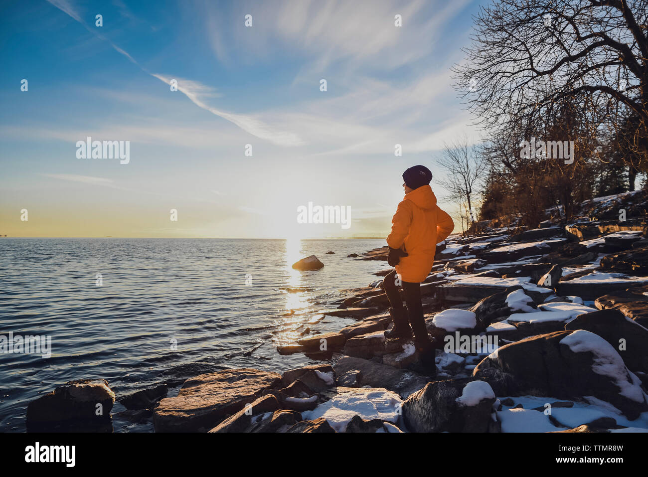 Boy standing alone on shoreline of lake at sunset on a winter evening. Stock Photo