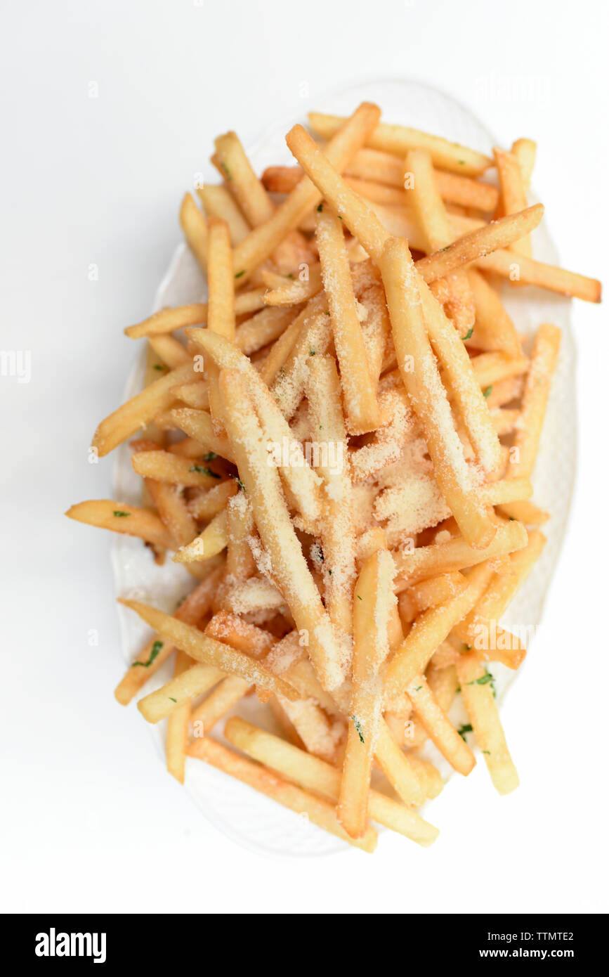 Overhead view of French fries in plate on white background - Stock Image