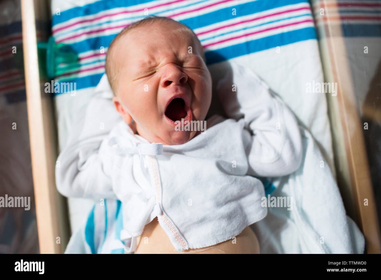 Close-up of baby boy yawning while sleeping in crib at hospital - Stock Image