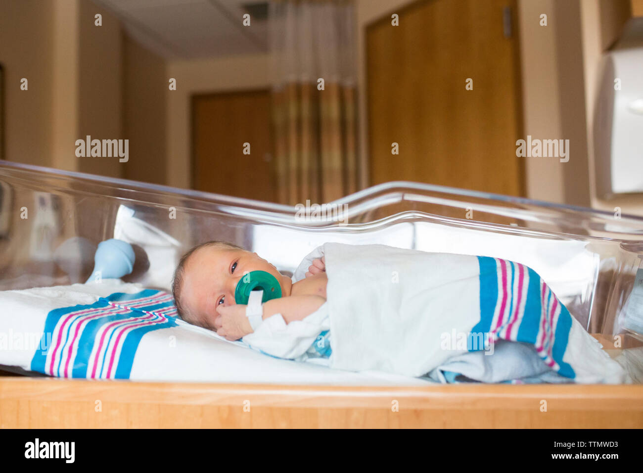 Portrait of baby boy with pacifier in mouth lying in crib at hospital Stock Photo