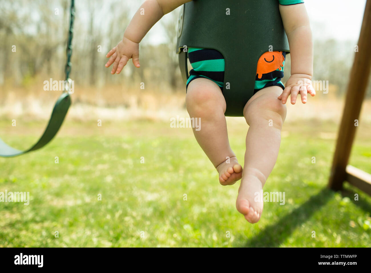 Low section of boy swinging in park - Stock Image
