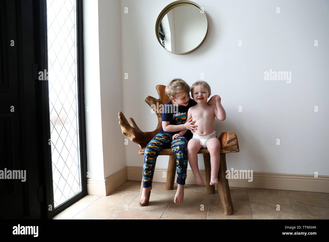 Happy Brothers Hug While Sitting on Indoors Organic Wooden Bench Stock Photo