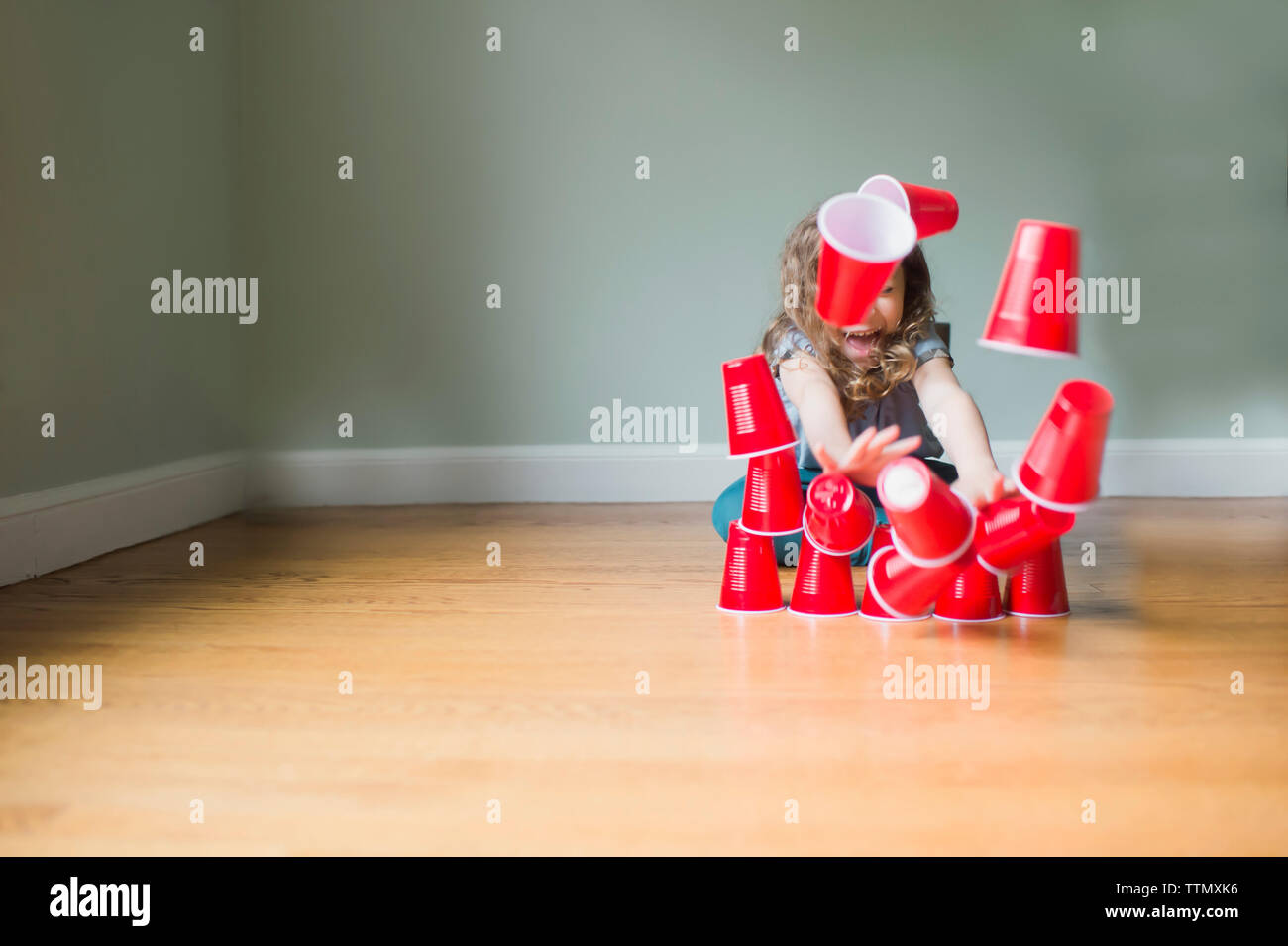 Playful girl breaking pyramid made of disposable cups while sitting on floor at home - Stock Image