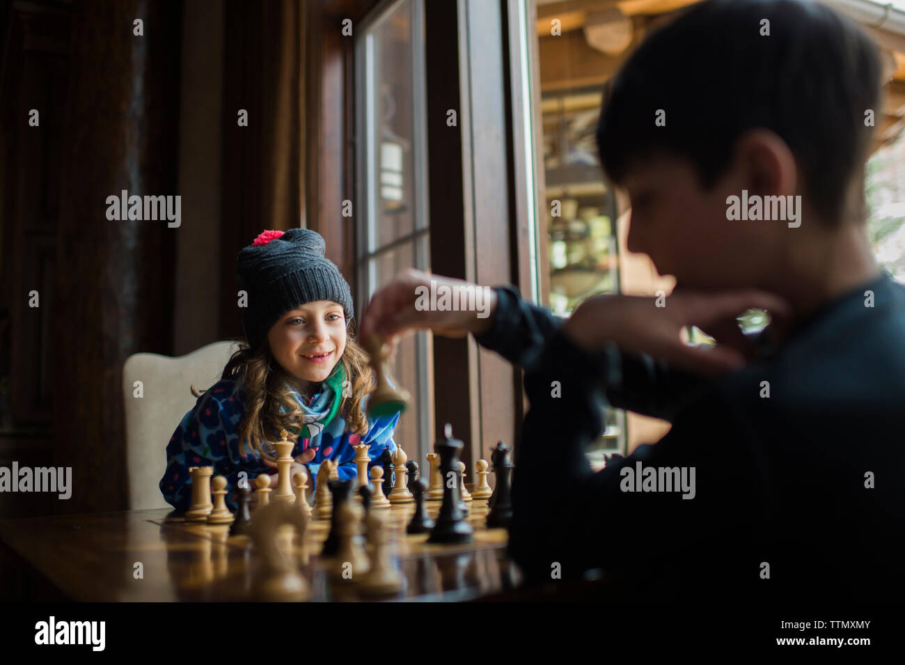 Siblings playing chess by window at home - Stock Image