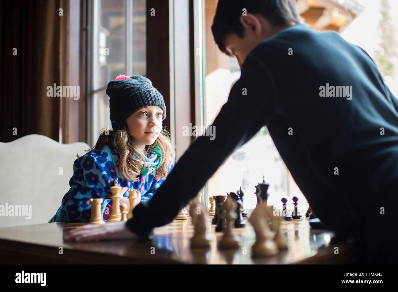 Siblings playing chess at home - Stock Image