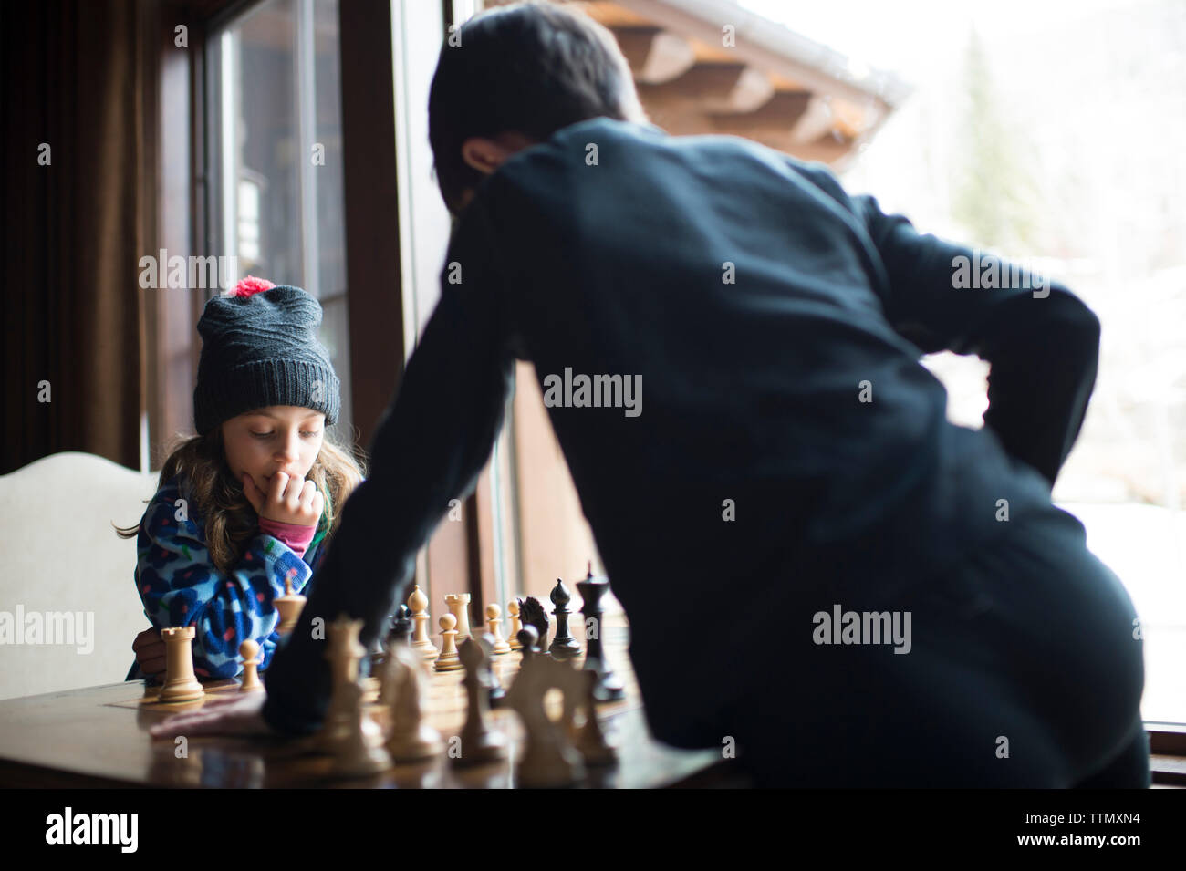 Siblings playing chess while standing by window at home - Stock Image