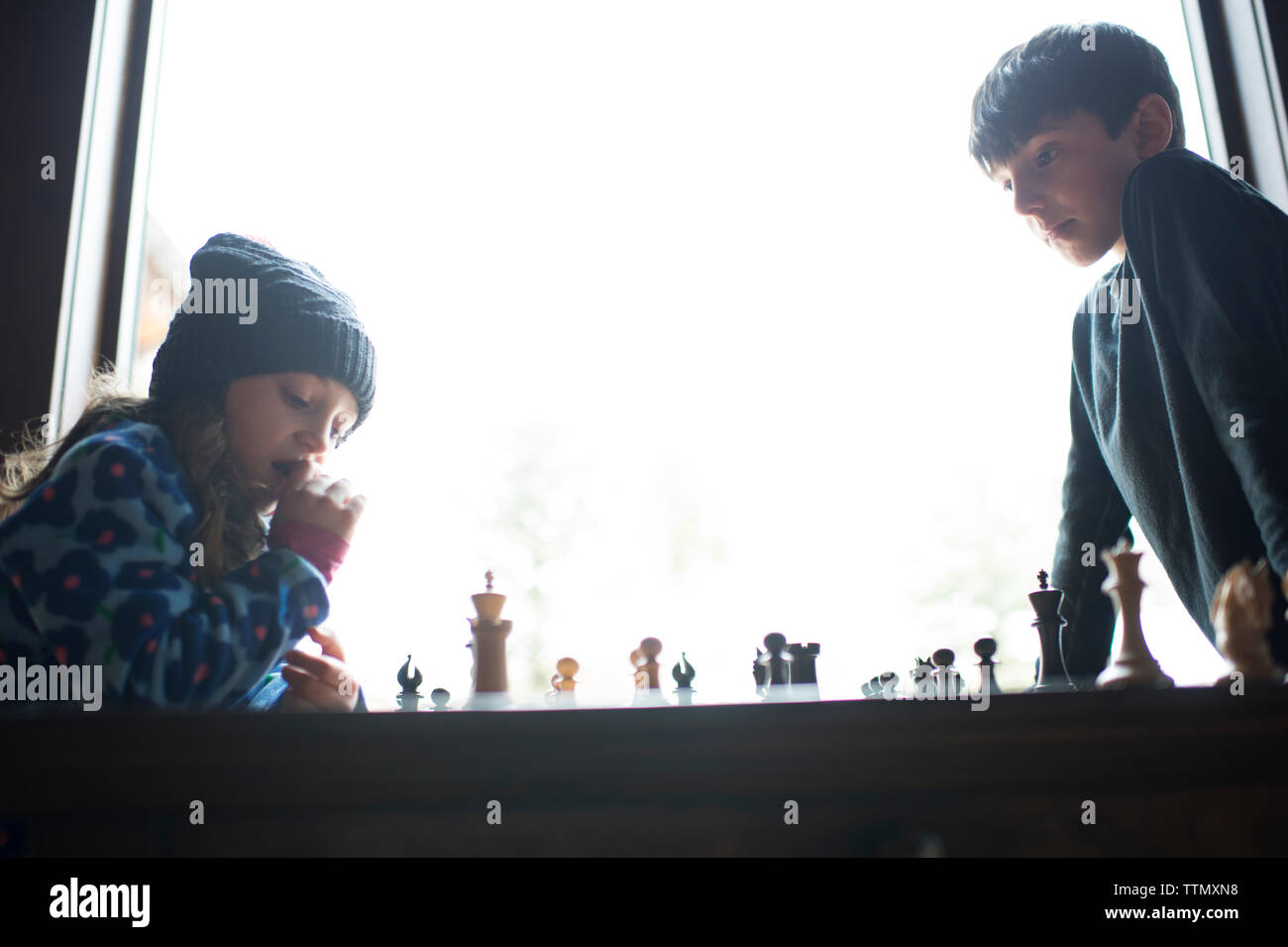 Low angle view of siblings playing chess by window at home - Stock Image
