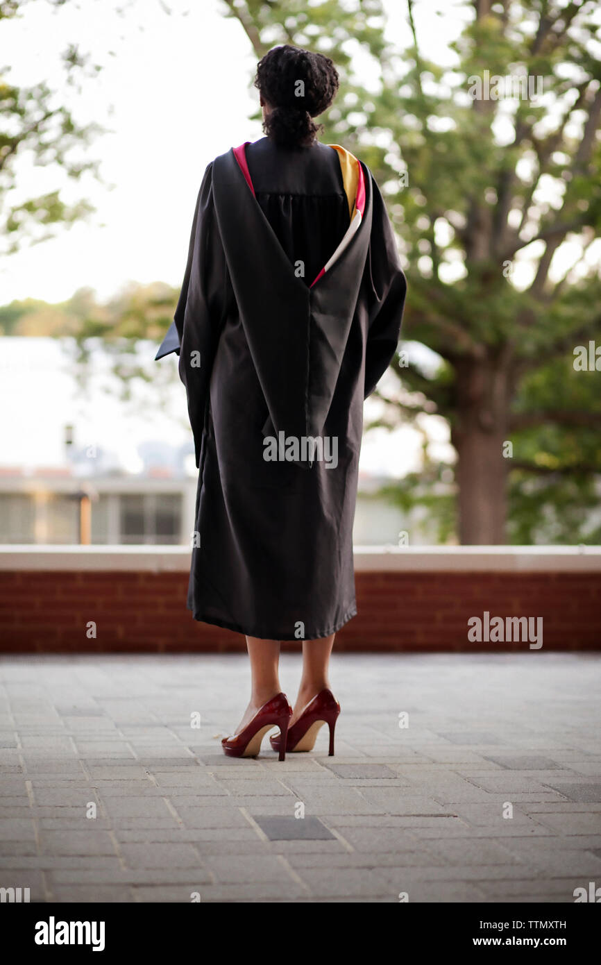Rear view of woman in graduation gown - Stock Image