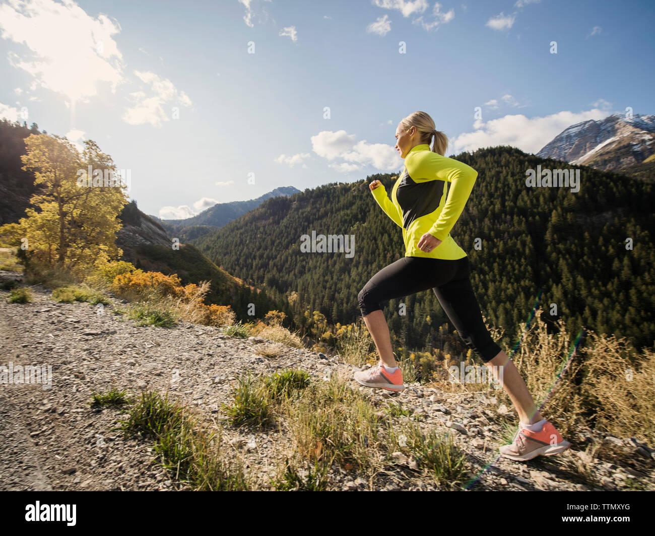 Healthy Caucasian woman running on mountain trail in autumn Stock Photo