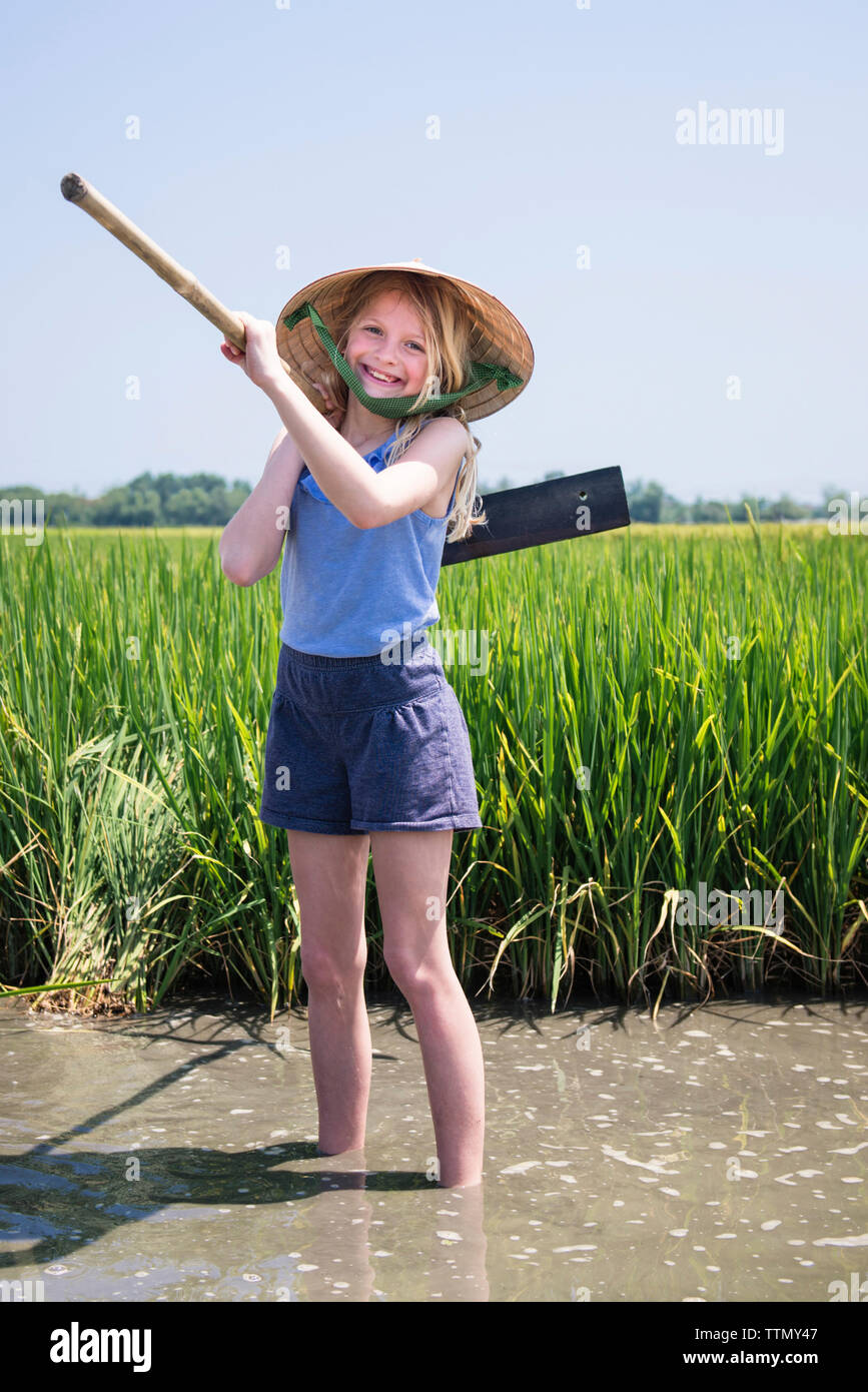 Portrait of happy girl carrying work tool while standing in muddy water against clear sky at farm during sunny day - Stock Image