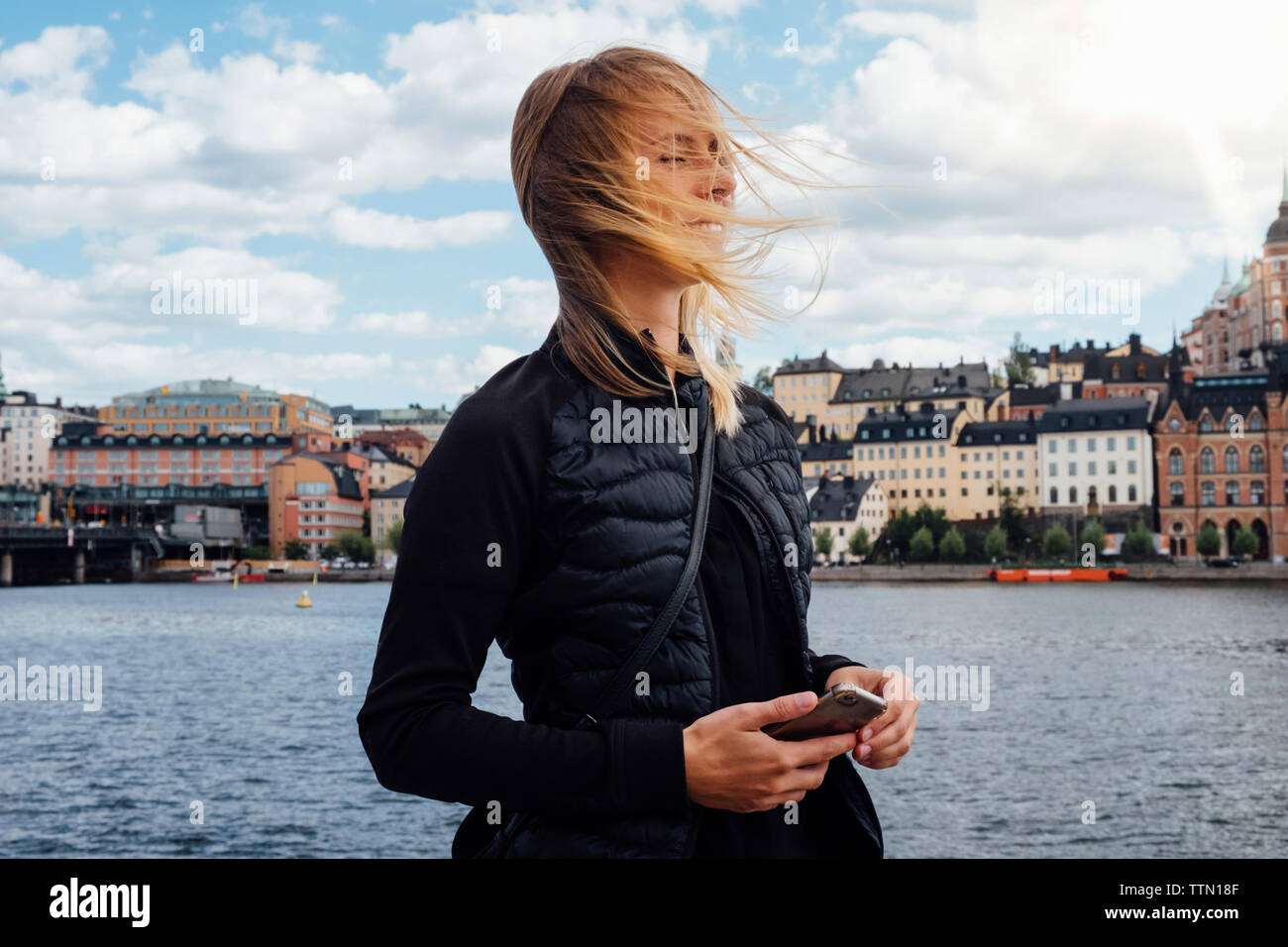 Smiling young woman with tousled hair standing by river in city - Stock Image
