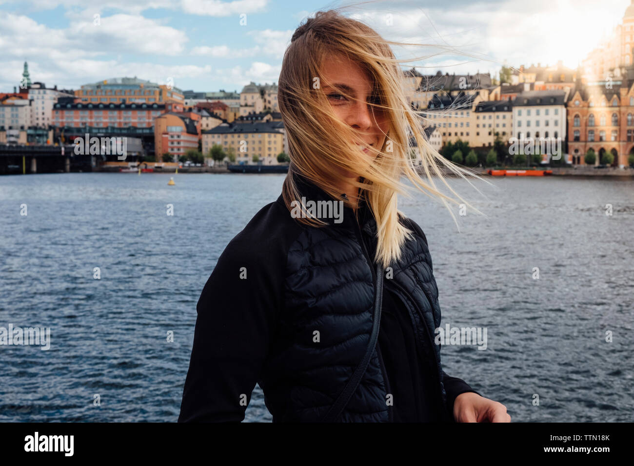 Portrait of smiling young woman with tousled hair standing against river in city - Stock Image