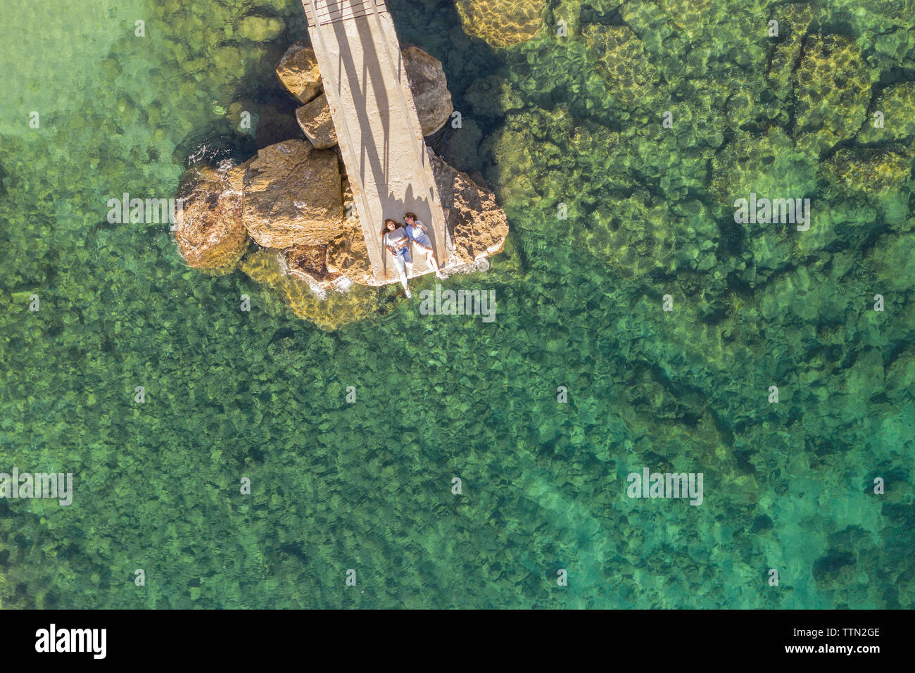 Drone view of female friends lying on pier over sea - Stock Image