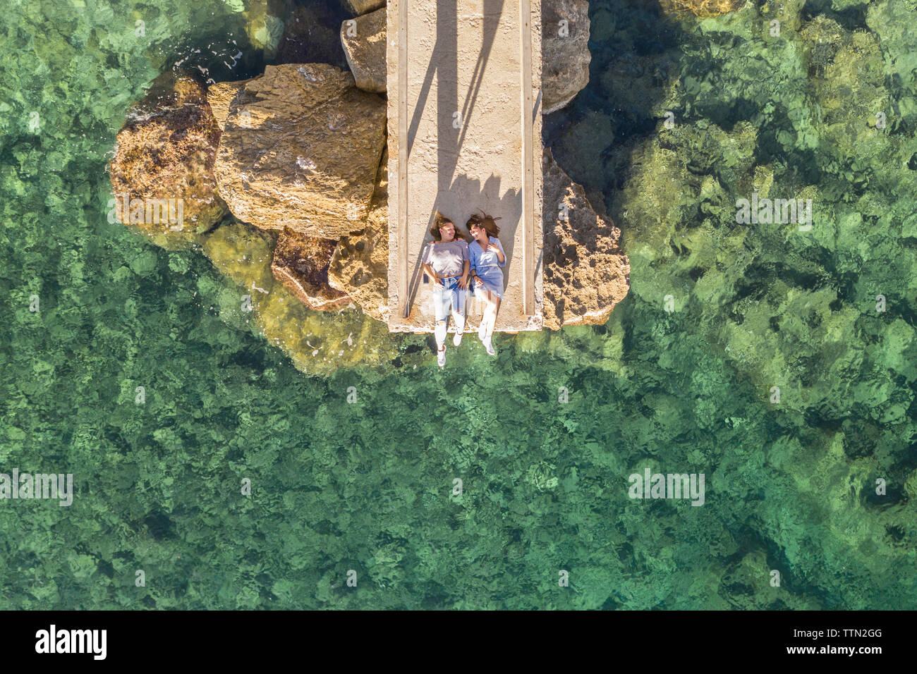 Drone view of female friends lying on pier over sea during sunny day - Stock Image